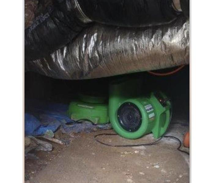 Crawlspace with green equipment.